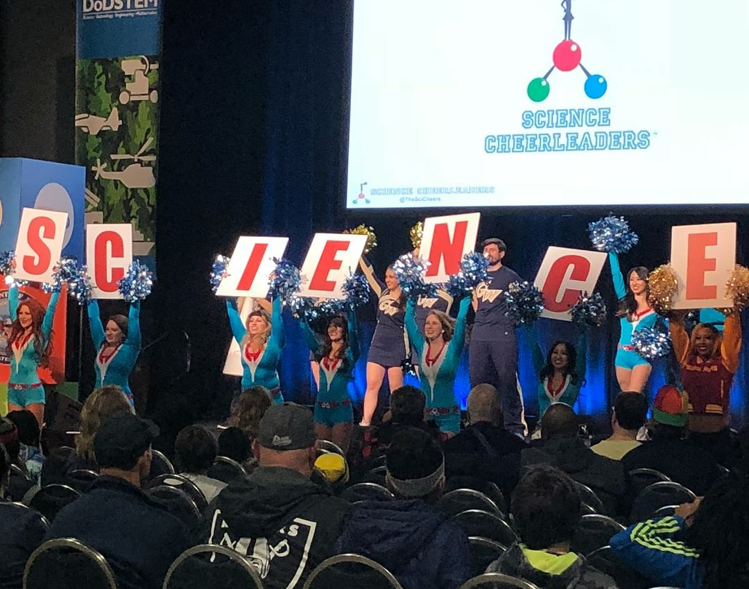 """Cheerleaders holding up letter signs that spell out """"science"""""""